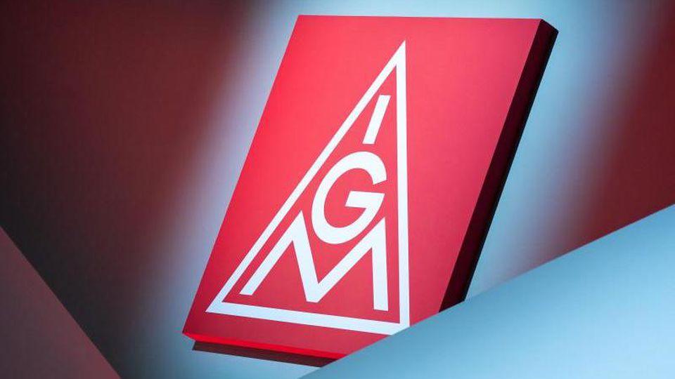 Das Logo der IG Metall hängt über einer Bühne. Foto: Daniel Karmann/dpa/Symbolbild