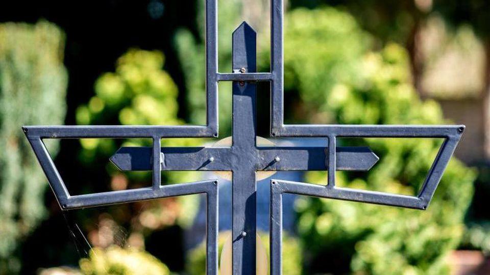 Ein Kreuz steht an einem Grab. Foto: Hauke-Christian Dittrich/dpa/Archivbild