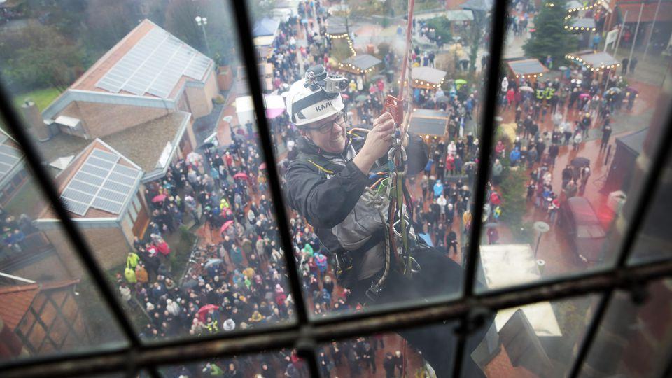 Pastor Christian Kopp klettert auf Kirchturm in Syke