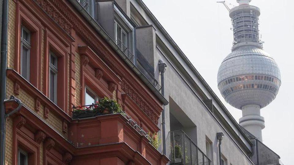 Eine Häuserfassade mit Wohnungen in Berlin-Mitte, hinter den Dächern ist der Berliner Fernsehturm zu sehen. Foto: Taylan Gökalp/dpa/Archiv