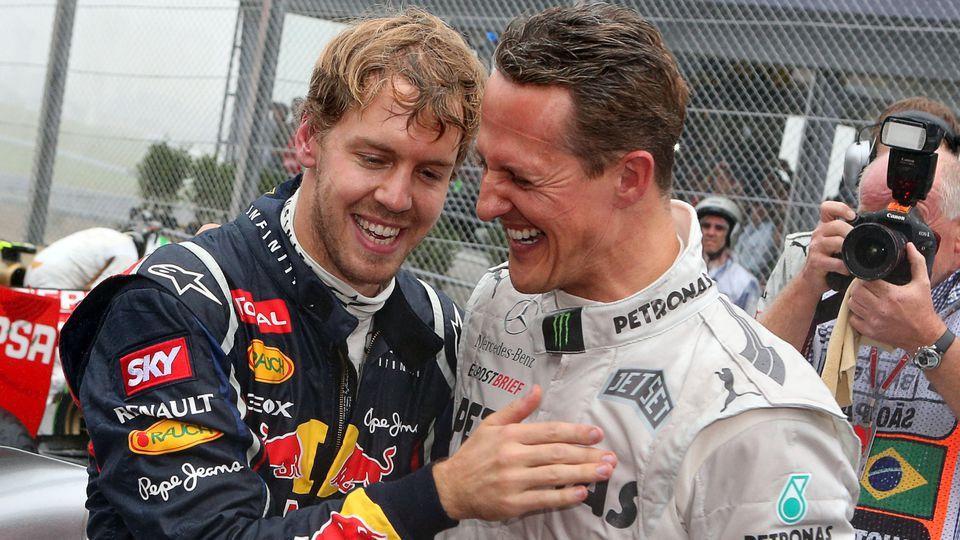 """ARCHIV - 25.11.2012, Brasilien, São Paulo: Der deutsche Formel-1-Fahrer Sebastian Vettel (l) feiert mit Michael Schumacher im Autodromo Jose Carlos Pace seinen dritten Weltmeistertitel in Folge. (zu dpa """"Vettel erinnert sich an Momente mit Vorbild Sc"""