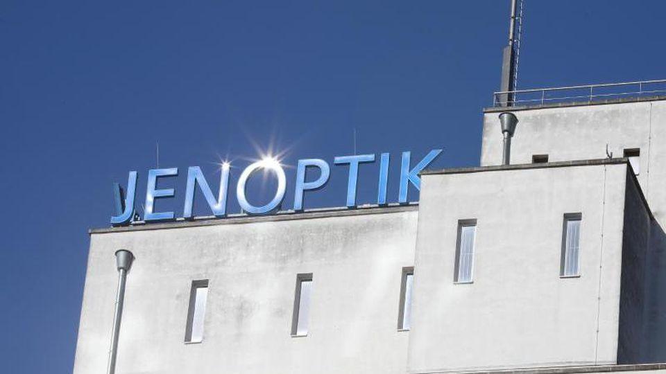 """Die Sonne spiegelt sich im Schriftzug """"Jenoptik"""". Foto: Bodo Schackow/zb/dpa/Archivbild"""