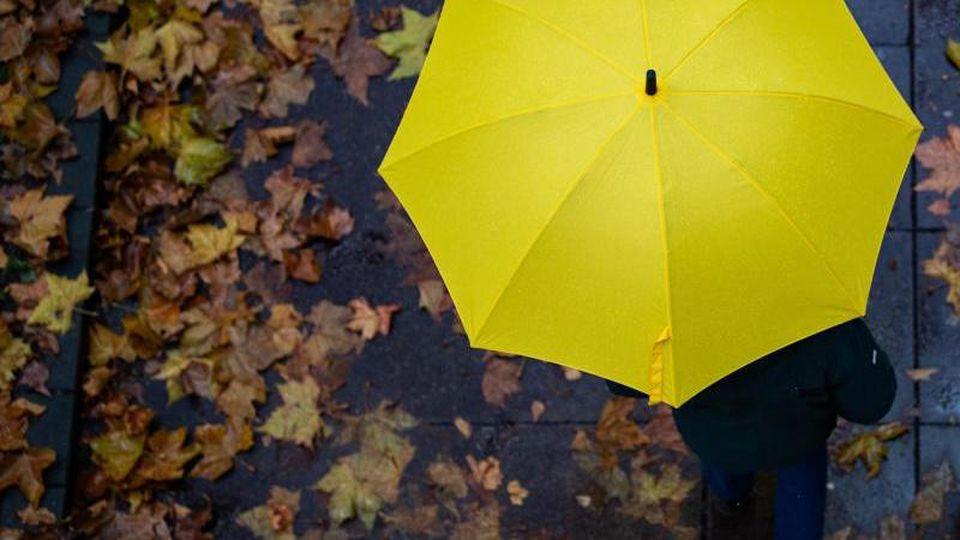 Eine Person läuft mit einem Regenschirm auf einem Gehweg. Foto: Tom Weller/dpa/Archivbild