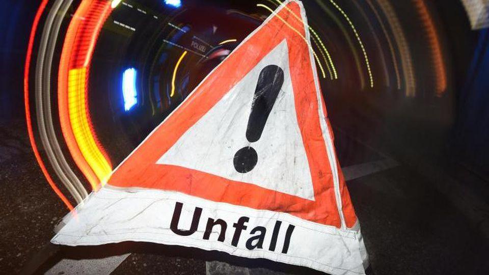 """Ein Warndreieck mit dem Schriftzug """"Unfall"""" steht auf einer Straße. Foto: Patrick Seeger/dpa/Symbolbild"""