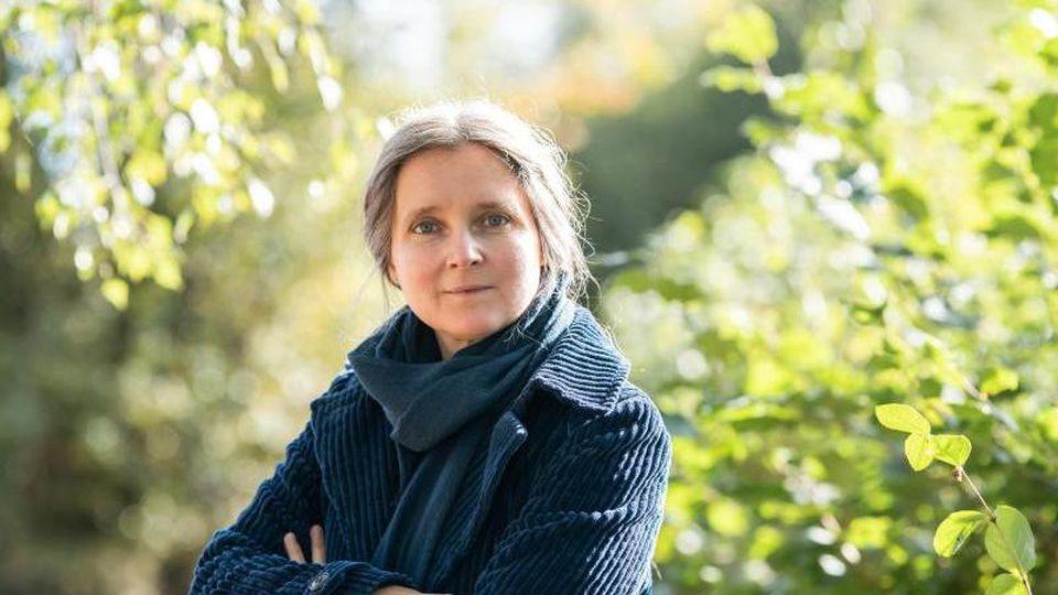 Marion Poschmann, Autorin, schaut im Garten des Ubbelohde-Haus in die Kamera. Foto: Silas Stein/dpa