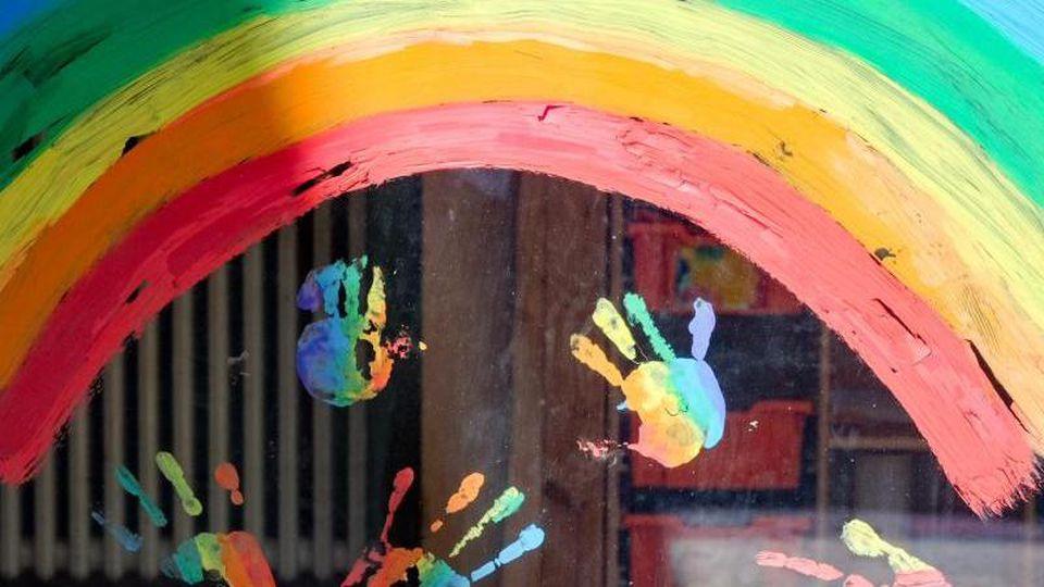 Kinderhände und ein Regenbogen sind an einer Kita zu sehen. Foto: Jens Kalaene/dpa/Archivbild