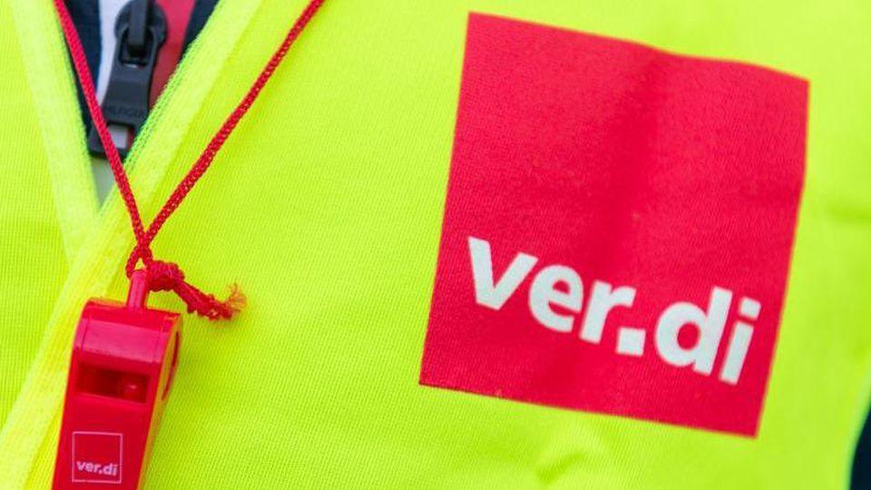 Ein Streikender trägt eine Warnweste mit dem Verdi-Logo und eine rote Trillerpfeife. Foto: Christophe Gateau/Archiv