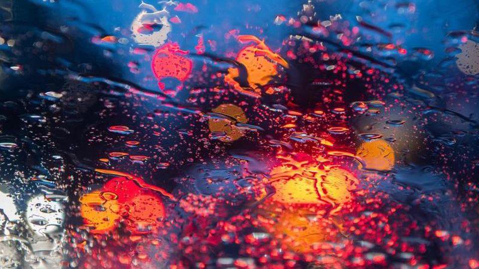Regentropfen sind auf einer Autoscheibe zu sehen. Foto: Robert Michael/dpa-Zentralbild/ZB/Symbolbild