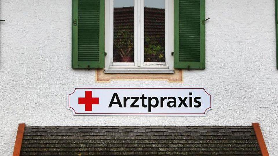 Ein Schild an einem Haus weist in einer kleinen Gemeinde auf eine Arztpraxis hin. Foto: Karl-Josef Hildenbrand/dpa/Symbolbild