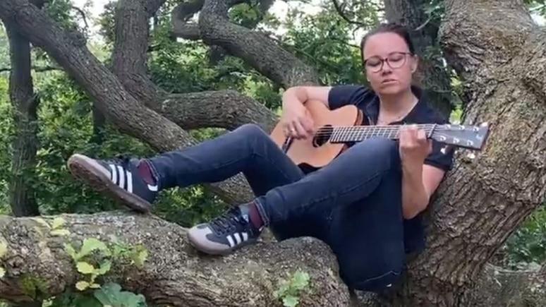 Michelle Müntefering singt mit Guitarre.