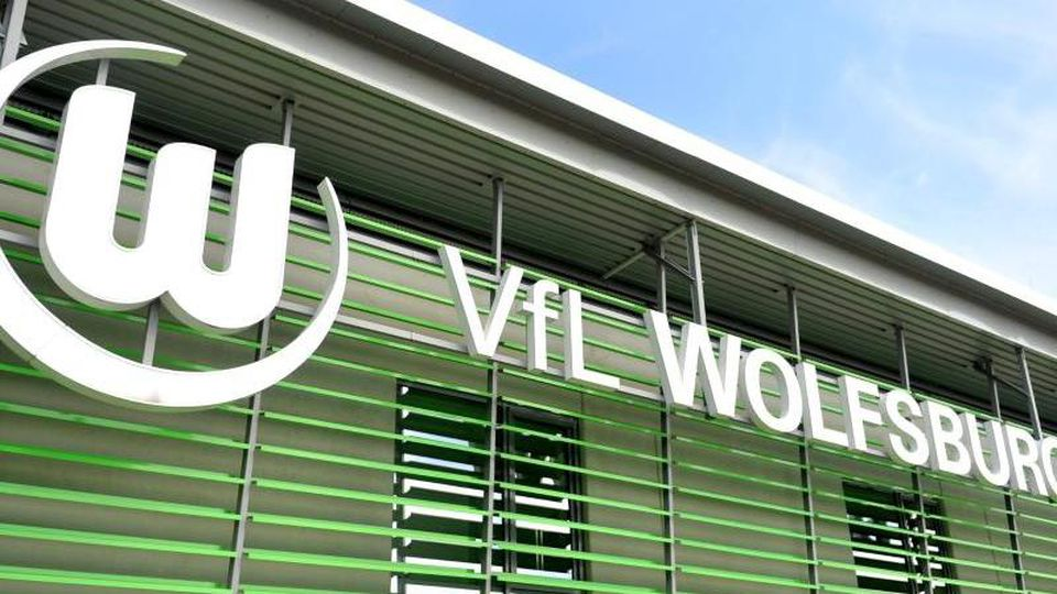 Das Logo des VfL Wolfsburg hängt über dem Eingang zum AOK-Stadion am Allerpark. Foto: Hauke-Christian Dittrich/dpa/Archiv
