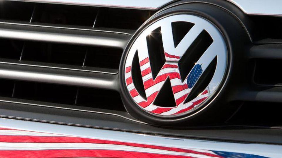 Die US-Fahne spiegelt sich in Logo und Kühlergrill eines VW. Foto: Friso Gentsch/dpa