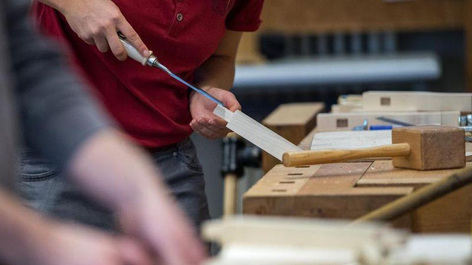 Auszubildende arbeiten in einer Berufsschule an einer Werkbank. Foto: Sebastian Gollnow/Archivbild