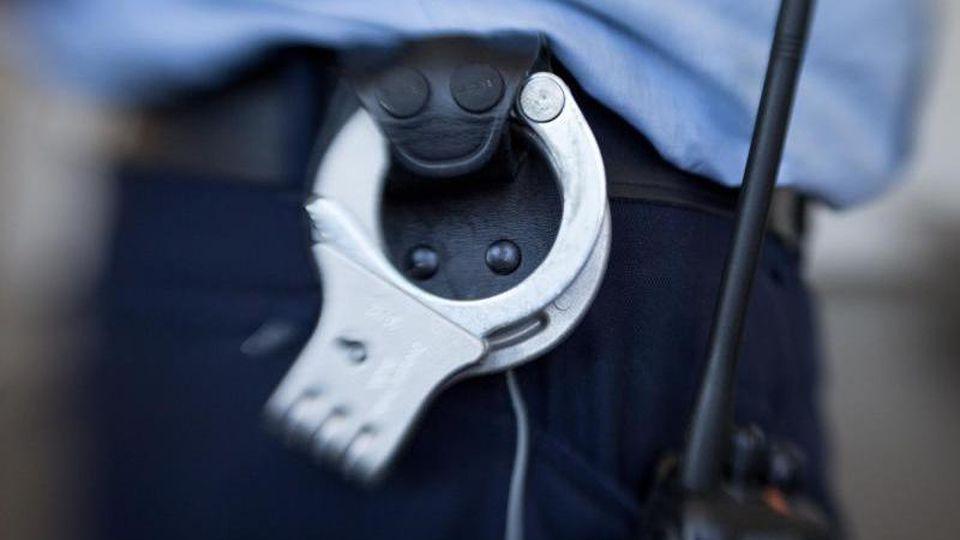 Handschellen hängen am Gürtel eines Justizbeamten. Foto: Friso Gentsch/dpa/Archivbild
