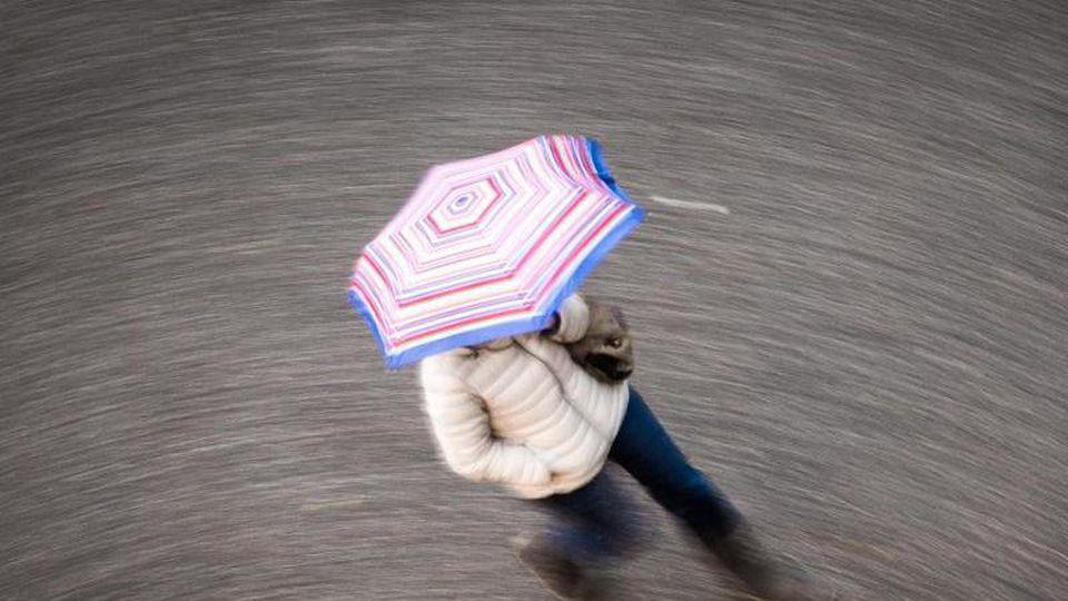 Eine Frau geht bei regnerischem Wetter über eine Straße. Foto: Frank Rumpenhorst/dpa/Symbolbild
