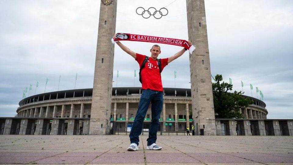 Bayern-Fan Piotr steht alleine vor dem Olympiastadion, in dem das DFB-Pokalfinale stattfindet. Foto: Christophe Gateau/dpa