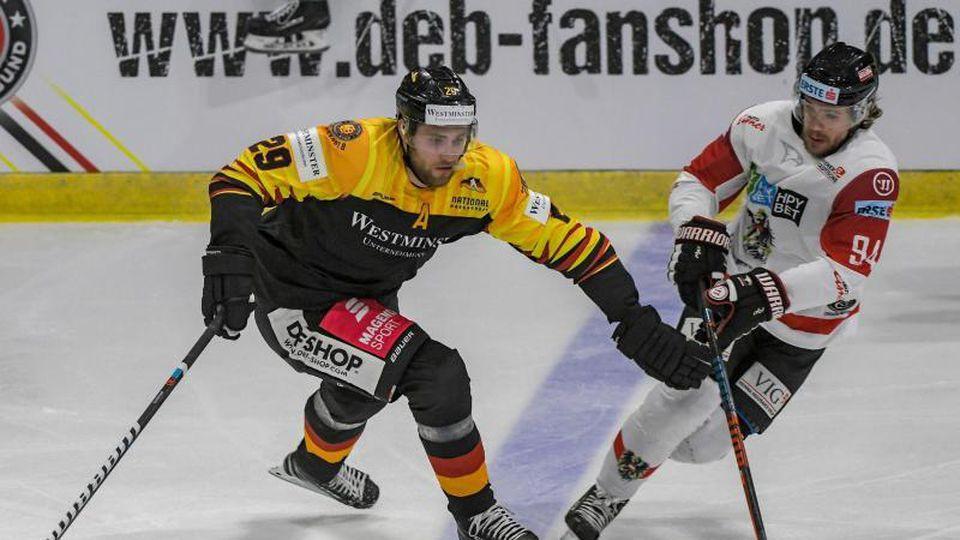 Leon Draisaitl von Deutschland und Marco Richter von Österreich (l-r.) im Zweikampf um den Puck. Foto: Armin Weigel