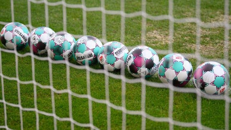 Bälle liegen auf dem Rasen. Foto: Robert Michael/dpa-Zentralbild/dpa/Symbolbild
