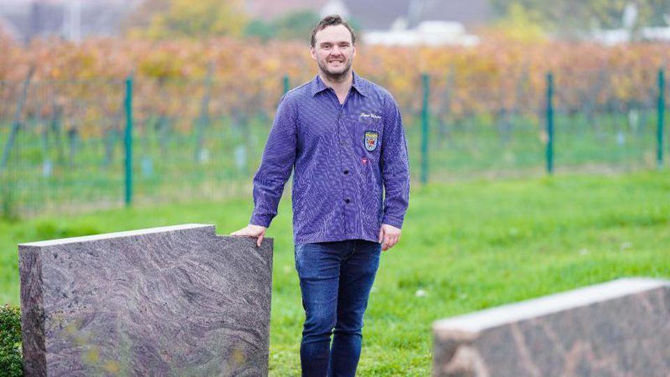 Timo Glaser, Ortsbürgermeister von Sankt Martin, steht auf dem Friedhof neben einem Grab. Foto: Uwe Anspach/dpa