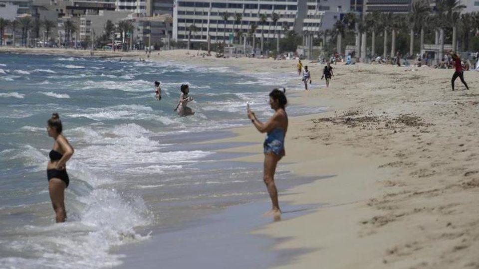 Menschen gehen am Strand von Arenal schwimmen. Foto: Clara Margais/dpa