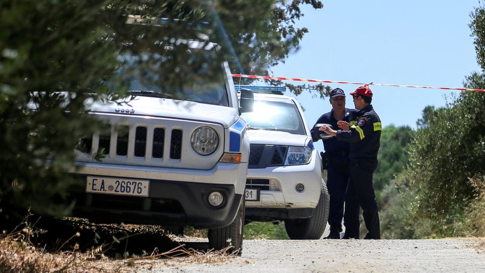 A police officer and a member of a fire brigade search and rescue team stand behind a police cordon, in an area where the body of a woman was found, near the village of Kolimpari on the island of Crete, Greece, July 9, 2019. REUTERS/Makis Kartsonakis