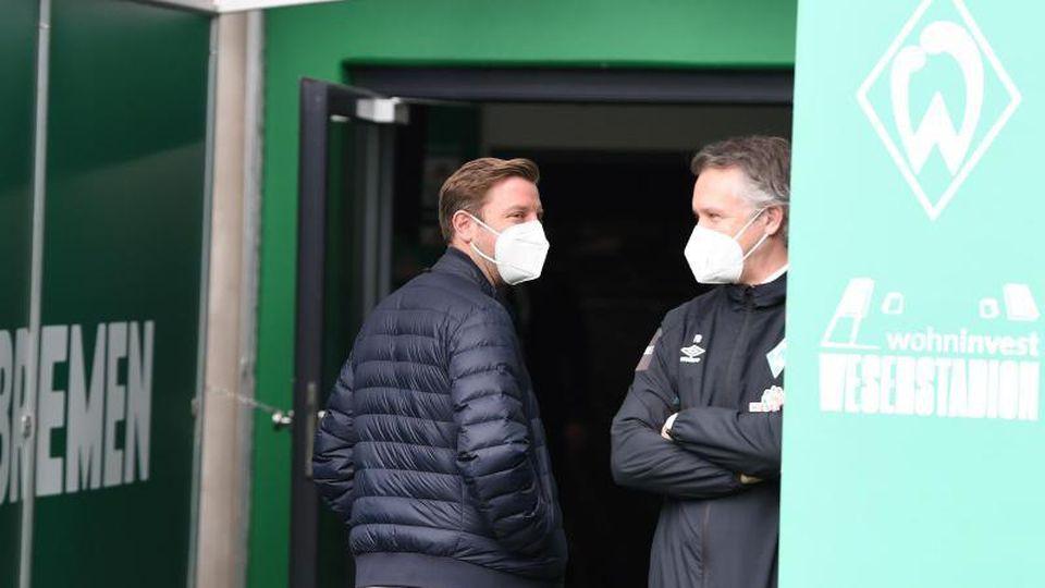 Werders Trainer Florian Kohfeldt (l) geht an Geschäftsführer Frank Baumann vorbei. Foto: Carmen Jaspersen/dpa/Archivbild