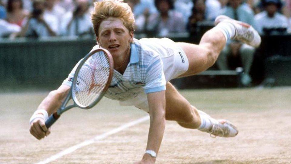 Der deutsche Tennisspieler Boris Becker hechtet während des Turniers in Wimbledon nach einem Ball. Foto: Rüdiger Schrader/dpa/Archivbild