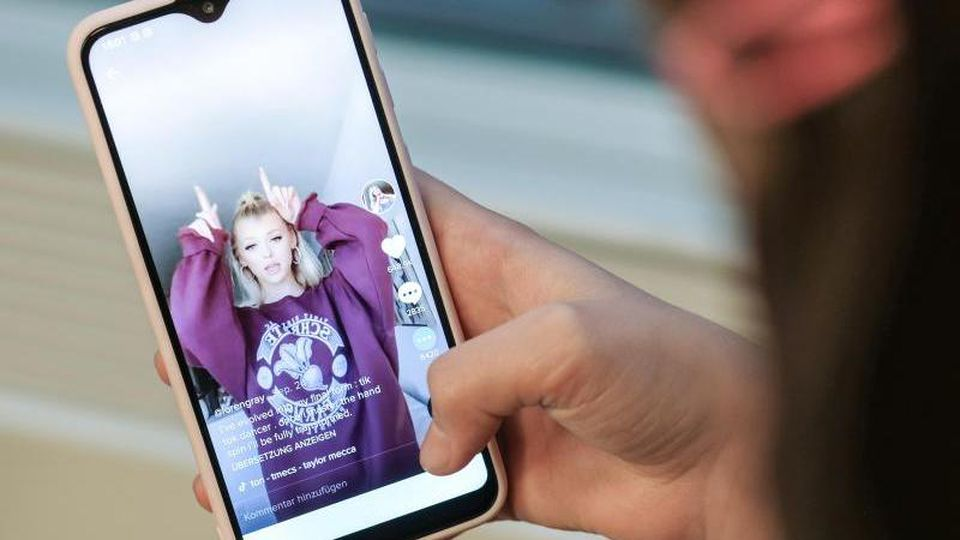 Ein Mädchen hält ihr Smartphone in den Händen, auf dem sie in der Kurzvideo-App TikTok das Profil von @lorengray geöffnet hat. Foto: Jens Kalaene/dpa-Zentralbild/dpa
