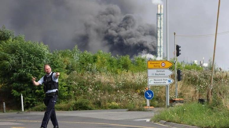 Ein Polizist steht unweit einer Zufahrt zum Chempark. Foto: Oliver Berg/dpa