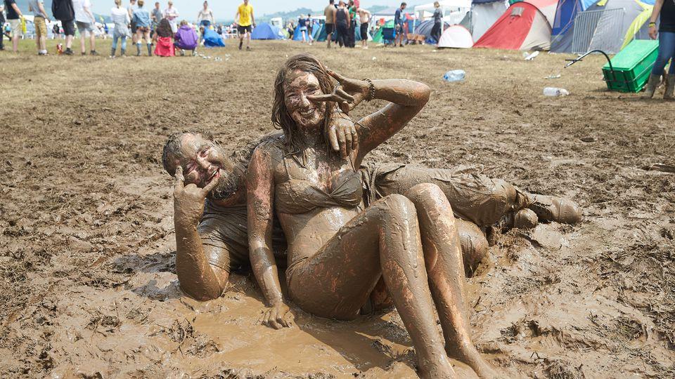 """Ein Paar wälzt sich beim Festival """"Rock am Ring auf dem Campinggelände im Schlamm"""