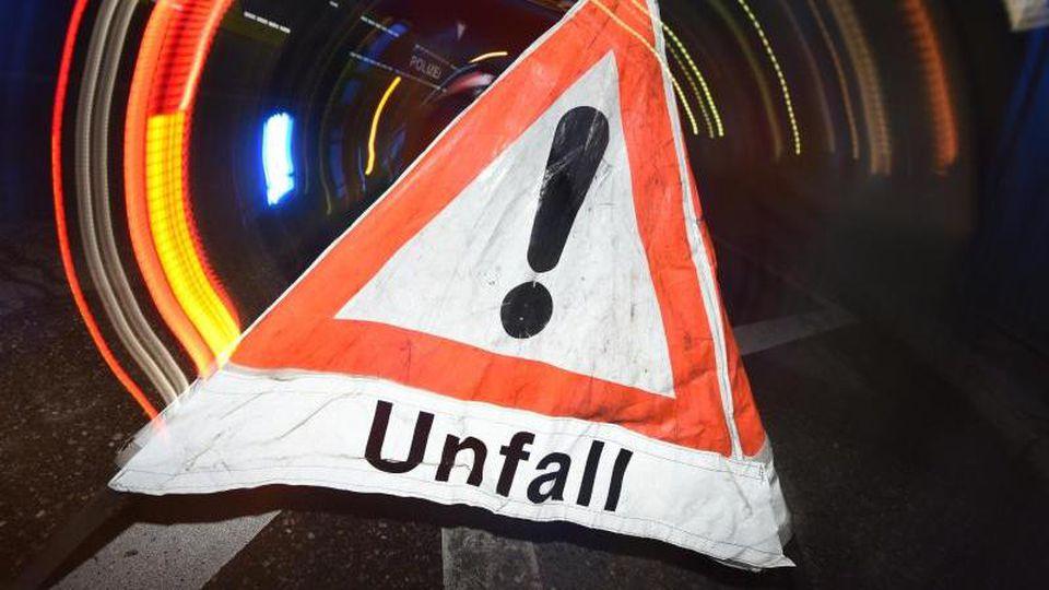 """Ein Warndreieck mit dem Schriftzug """"Unfall"""" steht vor einem Blaulicht auf der Straße. Foto: Patrick Seeger/dpa/Archivbild"""