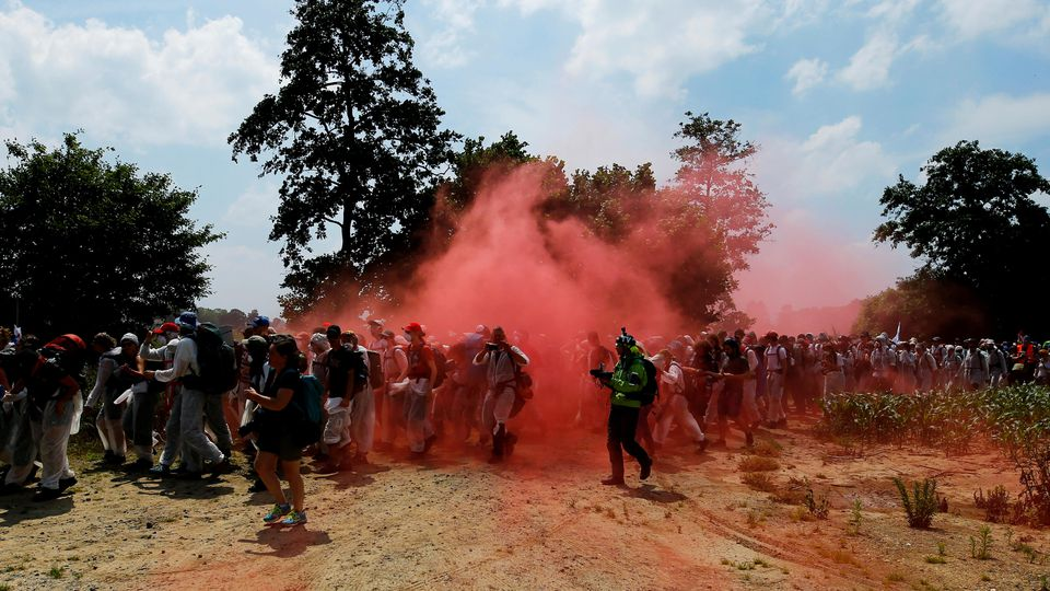 Environmental activists walk amid the red smoke from flares during a protest against the climate change near a pit of Garzweiler open cast brown coal mine near Duesseldorf, Germany June 22, 2019. REUTERS/Thilo Schmuelgen