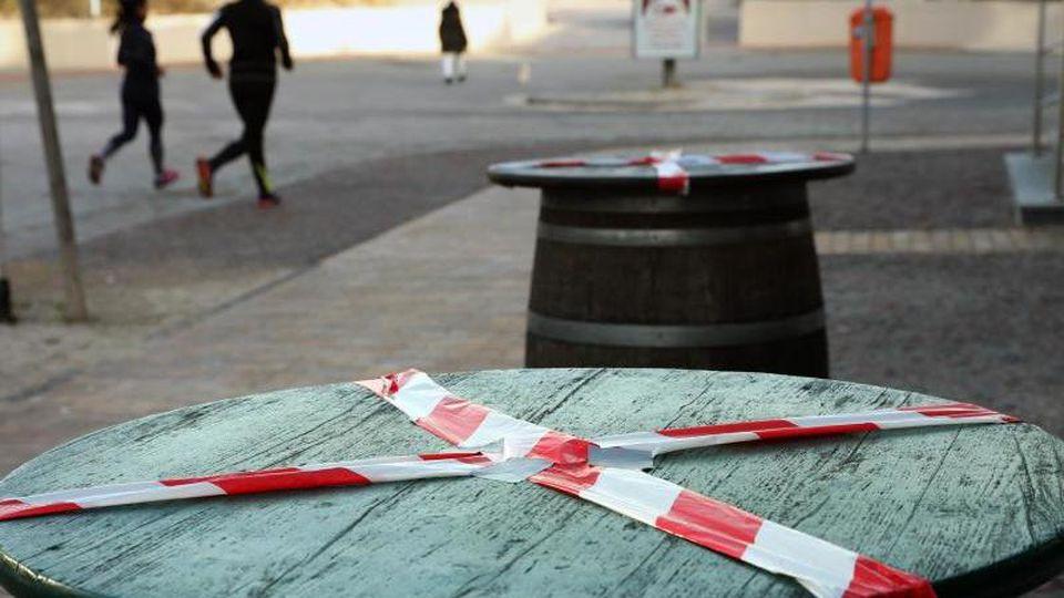 Kein gemütliches Beisammensein:Mit einem rot-weißen-Flatterband sind Stehtische an der Promenade des Ostseebades Warnemünde abgeklebt. Foto: Bernd Wüstneck/dpa-Zentralbild/dpa