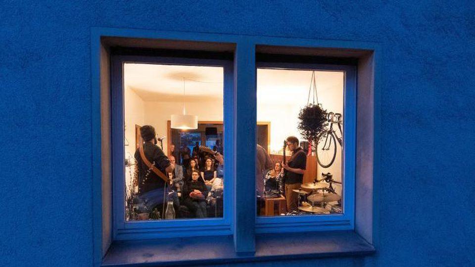 Mit Blick durch ein Fenster von einer Straße aus sieht man eine Band in einer Wohnung. Foto: Friso Gentsch
