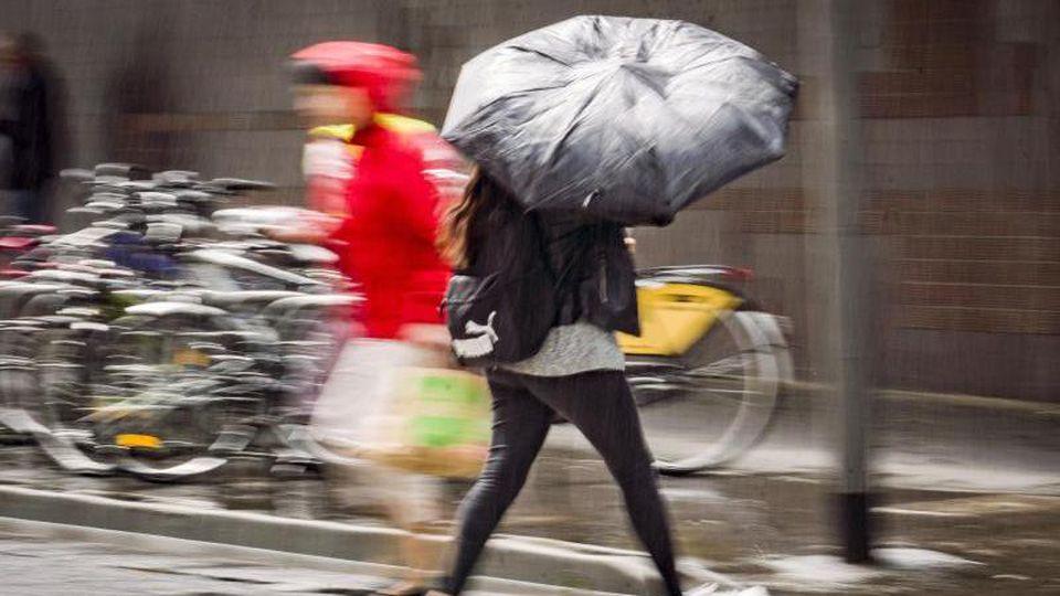 Eine Frau überquert bei einem Regenschauer eine Straße. Foto: Frank Rumpenhorst/Archivbild