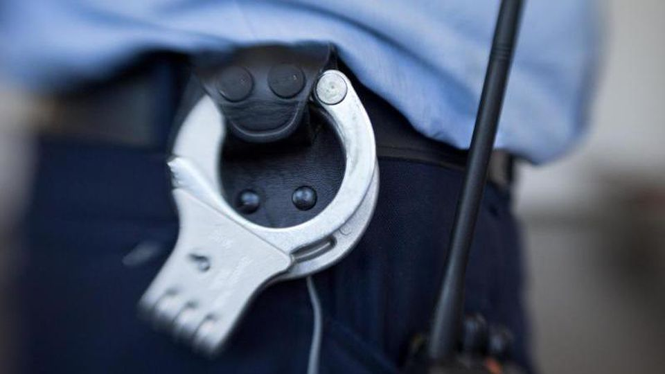 Blick auf die Handschellen eines Justizbeamten im Landgericht. Foto: Friso Gentsch/dpa/Symbolbild