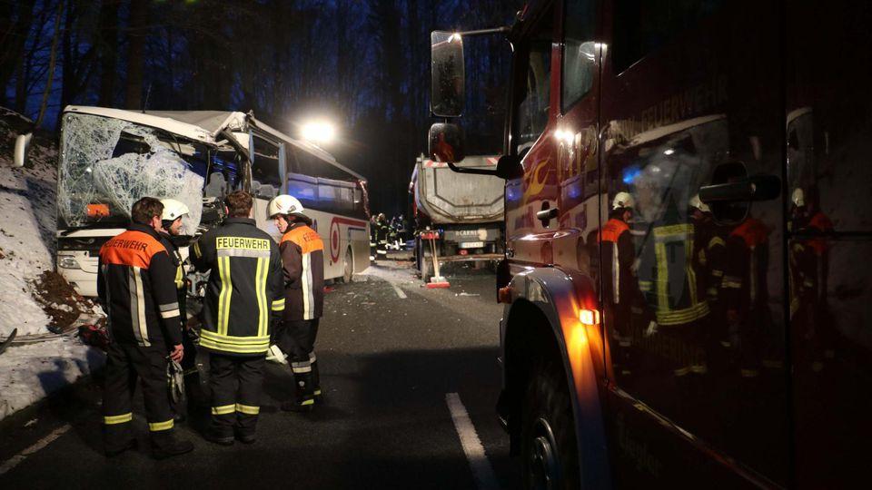 Fürstenstein: Feuerwehrleute stehen nach einem vor einem beschädigten Bus. Bei einem Unfall mit dem Schulbus und einem Lastwagen ist der Fahrer des Sattelschleppers ums Leben gekommen.