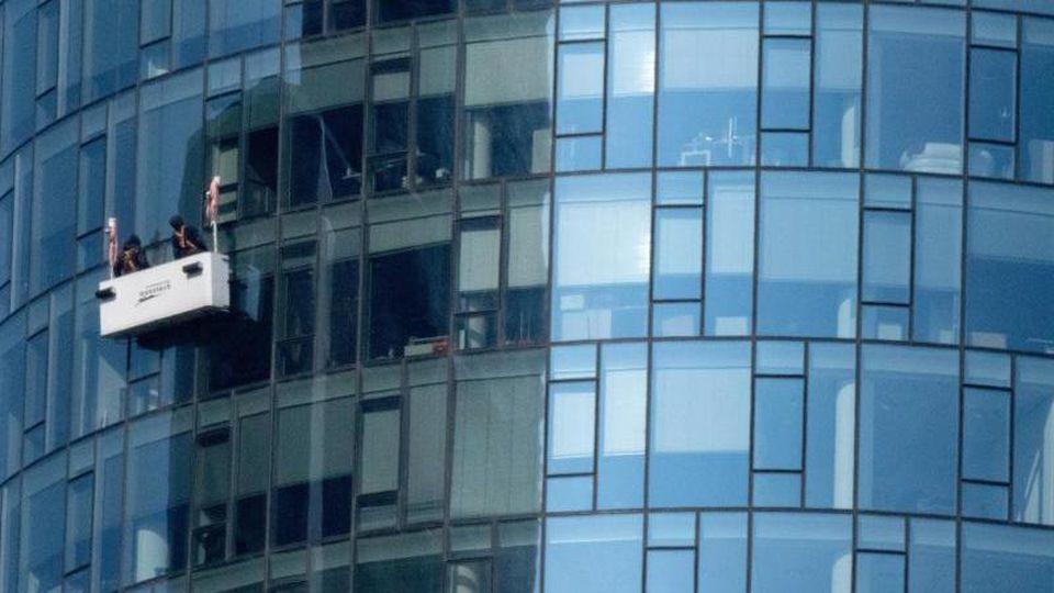 Aus einer Gondel heraus säubern zwei Fensterputzer die Fassade des Helaba-Towers in der Frankfurter Innenstadt. Foto: Boris Roessler/Archiv