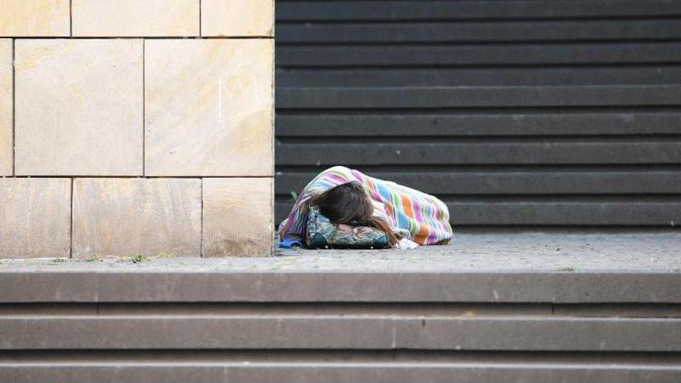 Eine Obdachlose schläft auf den Stufen vor der Frankfurter Kunsthalle Schirn. Foto: Arne Dedert/dpa/Archivbild