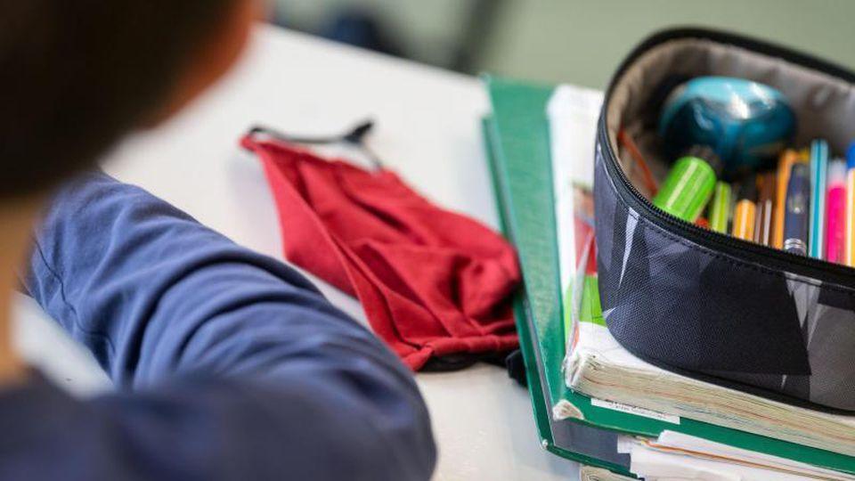 Eine Mund-Nasen-Bedeckung liegt während einer Unterrichtsstunde auf einem Schultisch. Foto: Marijan Murat/dpa/Symbolbild