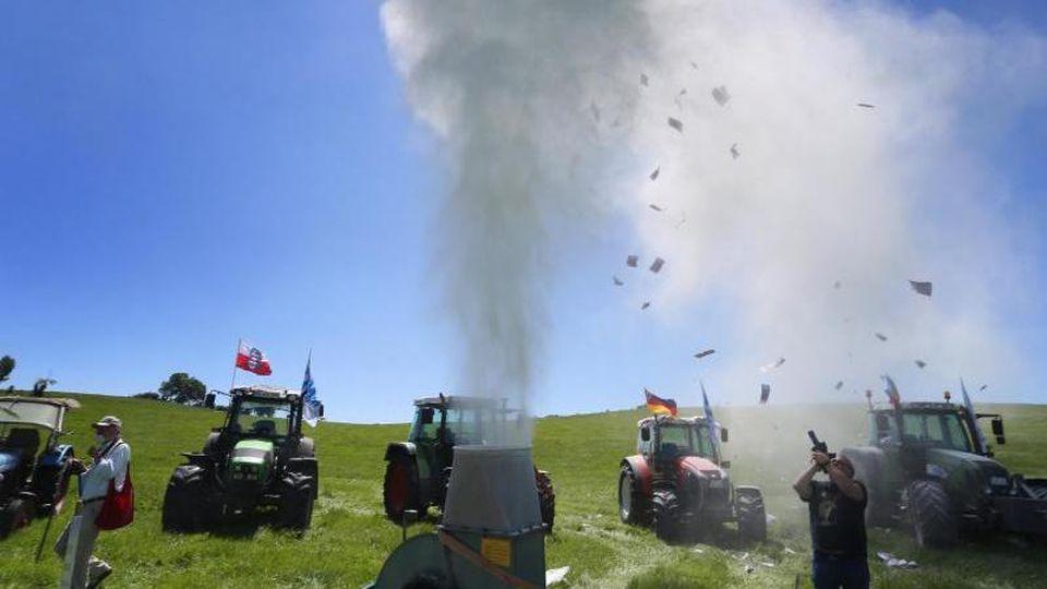 Milchpulver wird auf einer Protestaktion des Bundesverbandes der Deutschen Milchviehhalter die Luft geblasen. Foto: Karl-Josef Hildenbrand/dpa/Archivbild