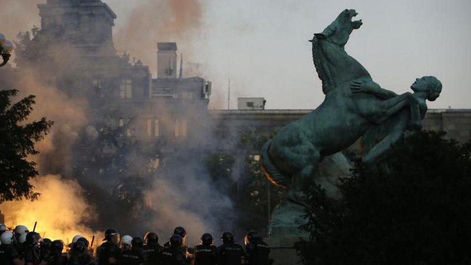Demonstranten zünden bei einem Zusammenstoß mit Polizisten Fackeln an. Foto: Darko Vojinovic/AP/dpa