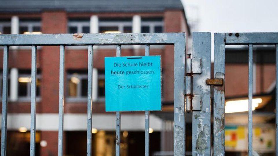 """Ein Hinweis """"Die Schule bleibt heute geschlossen, Der Schulleiter"""" hängt am Eingang des Gymnasiums. Foto: Jonas Güttler/dpa"""