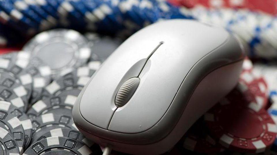 Eine Computermaus liegt auf einem Stapel Glücksspiel-Jetons. Foto: picture alliance/dpa/Archivbild