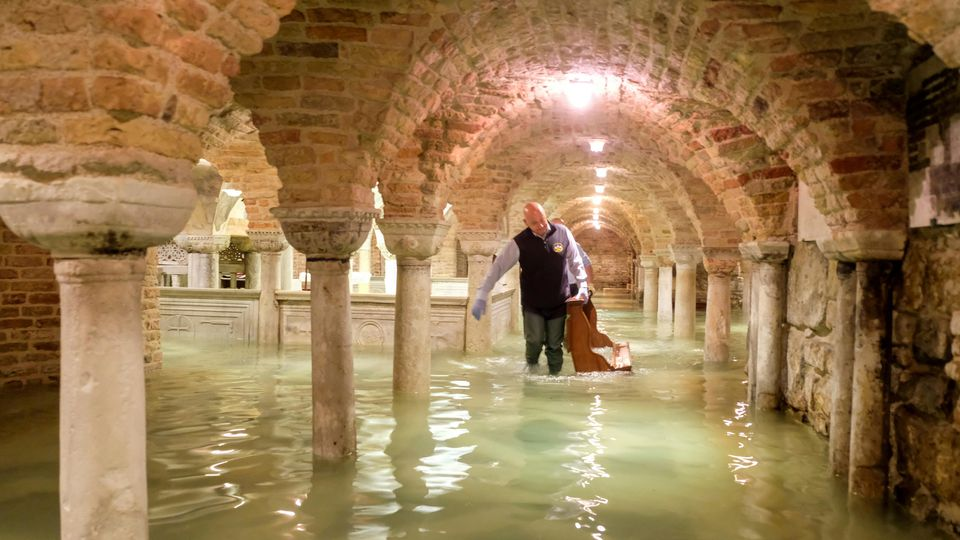 FILE PHOTO: A man wades in the flooded crypt of St Mark's Basilica during a period of exceptionally high water levels in Venice, Italy November 13, 2019. REUTERS/Manuel Silvestri/File Photo
