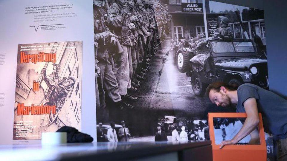 Tischler Paul Winkler installiert eine Stele in der neuen Dauerausstellung in der Gedenkstätte. Foto: Ronny Hartmann/dpa/Archivbild