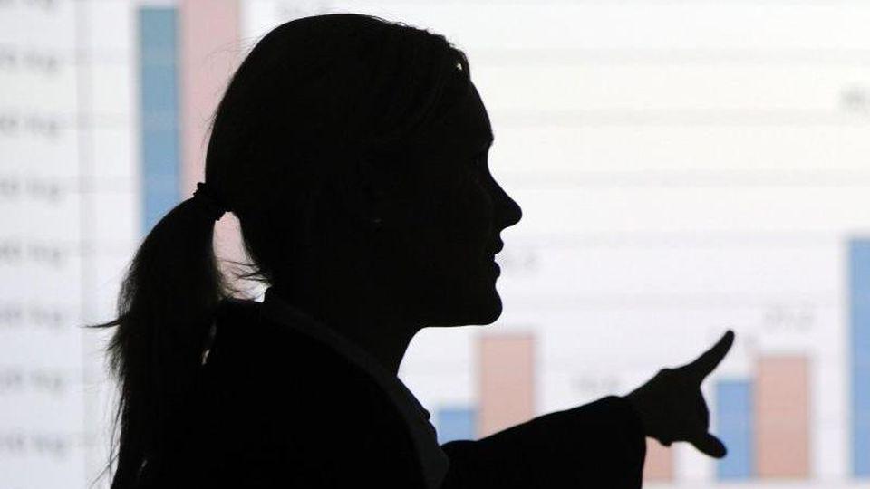 Eine Frau erklärt eine mittels Beamer an die Wand projizierte Statistik. Foto: picture alliance / dpa/Illustration