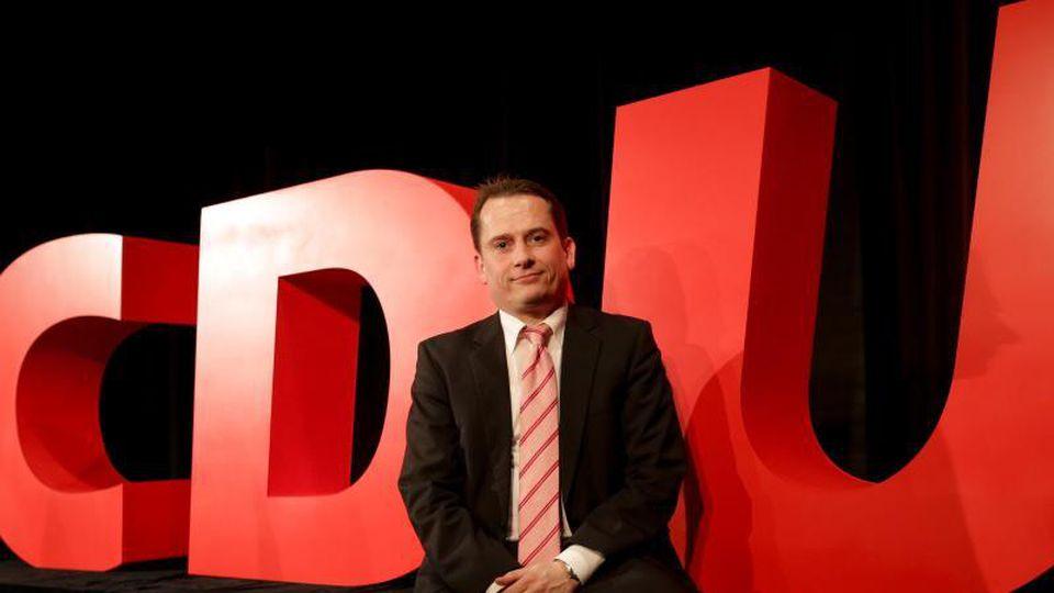 Roland Heintze, Landesvorsitzender der Hamburger CDU, vor dem Logo seiner Partei. Foto: Axel Heimken/Archiv