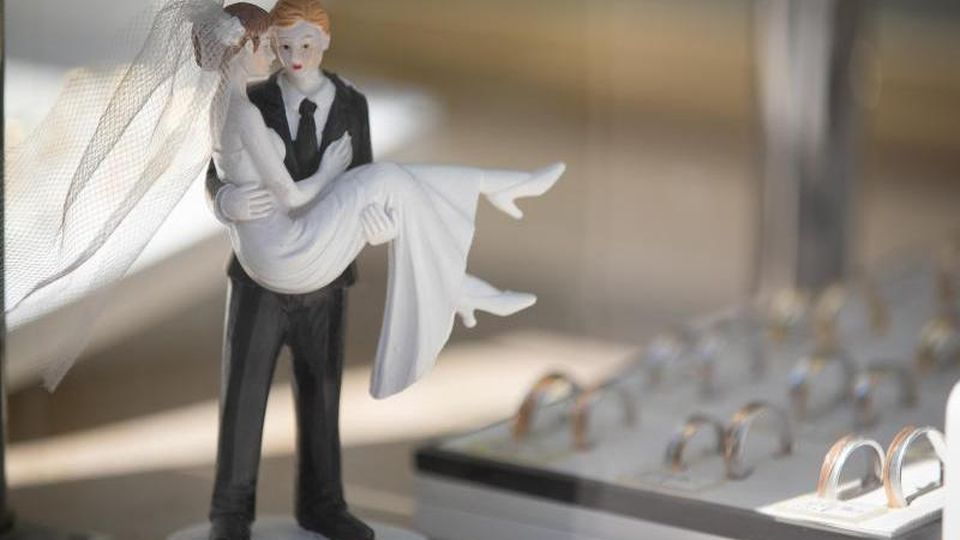 Hochzeitspaar-Figuren stehen in der Auslage eines Juweliers. Foto: Friso Gentsch/dpa/Symbolbild