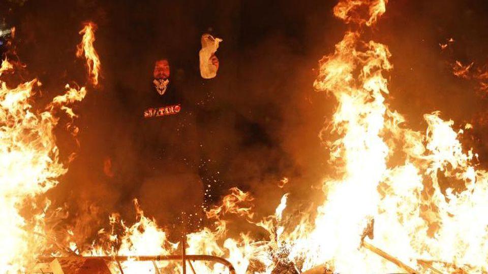 Ein Demonstrant steht vor einer brennenden Barrikade. Foto: Emilio Morenatti/AP/dpa